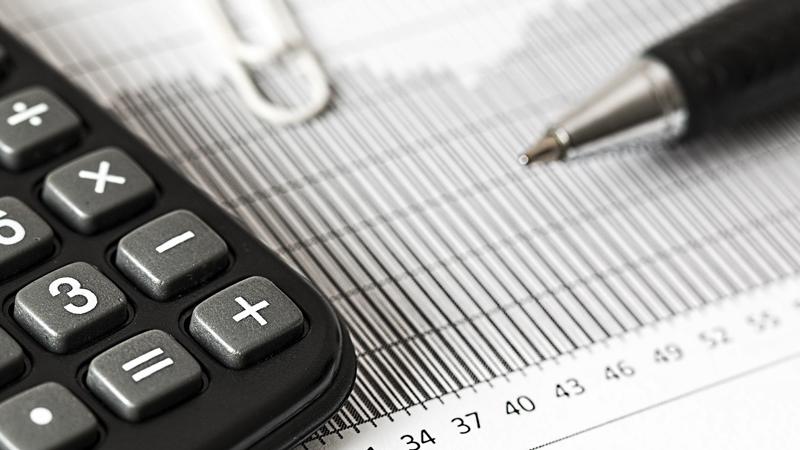 Papel com calculadora, caneta e clips